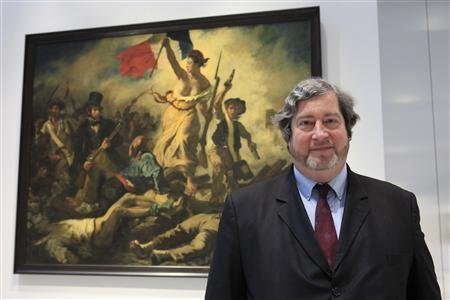 "Reuters/Reuters - Vincent Pomarede, curator of painting department at the Louvre Lens Museum, poses front of Eugene Delacroix 's painting, ""Liberty Leading the People (28 July 1830) (La Liberte guidant le peuple) in ""La Galerie du Temps"" (Gallery of Time) during a media day on the eve of the inauguration of the Le Louvre Lens Museum, in Lens, northern France, in this December 3, 2012 file photo. REUTERS/Pascal Rossigno"
